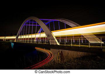 Railway bridge with train and car lights at night