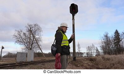 Railway electrician with cable talking on phone near signal...