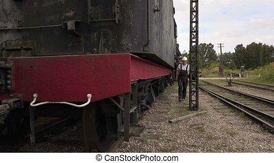 Railway employee climbs up on locomotive
