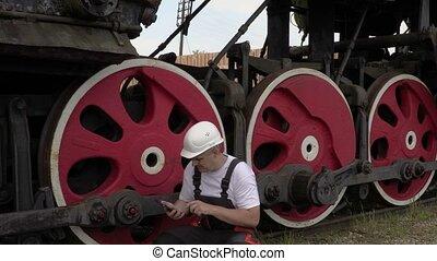 Railway employee on the locomotive running gear