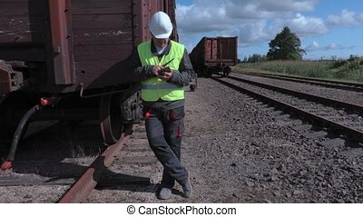 Railway employee on walkie talkie and tablet PC near wagons