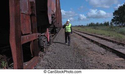 Railway employee on walkie talkie inspecting wagons