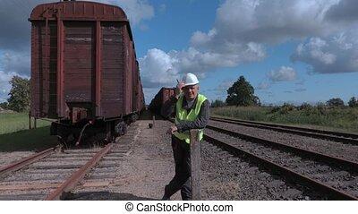 Railway employee showing stop gestures near wagons