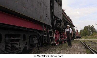 Railway employee talking and walking near locomotive