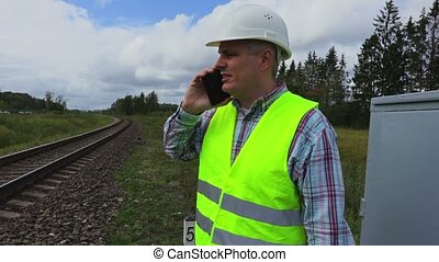 Railway employee talking on smart phone