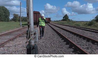 Railway employee walking and talking on phone near wagons
