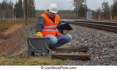 Railway employee with adjustable wrench near railway