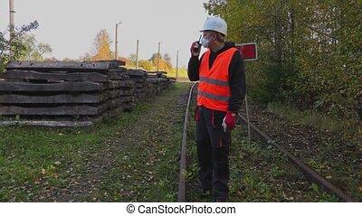 Railway Engineer in the air mask on walkie-talkie