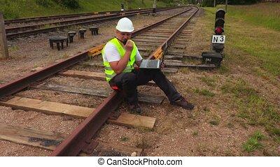 Railway Engineer with laptop on walkie talkie