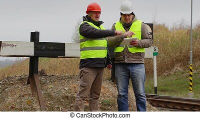 Railway engineers with tablet PC near the railway