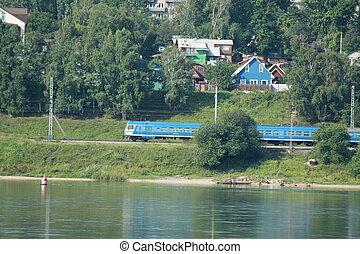 Train moves on railway along Angara river