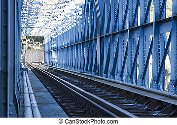 railway line passing through metallic blue tunnel