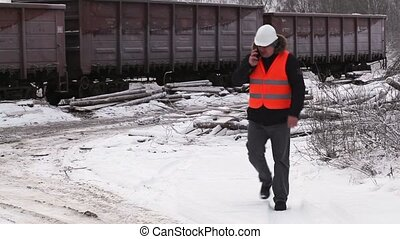 Railway officer walking near freight wagons