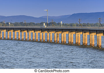 Railway or railroad crossing the lake in morning light