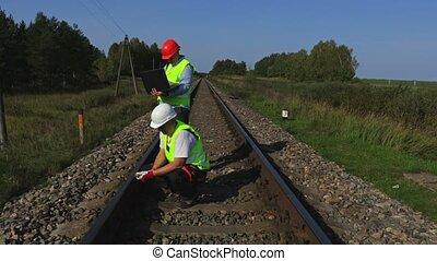 Railway staff checks railway condition in summer day