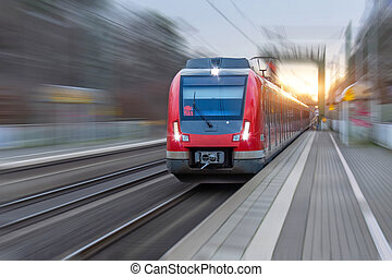 Railway station with head locomotive high speed commuter train with motion blur effect