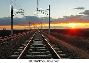 Railway at a sunset with sun and clouds