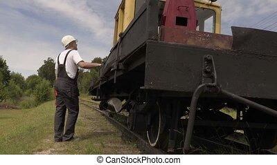 Railway talking and show thumb up near railway machinery