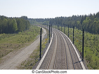Railway track - A high speed, modern railroad thru a green...