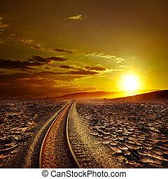 Railway track crossing drought desert under sunset sky