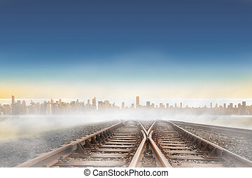 Railway tracks leading to city on the horizon