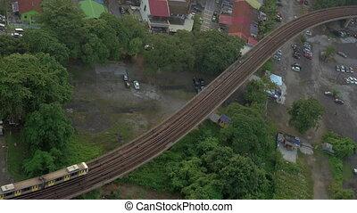 Railway with a passing train in city of Kuala Lumpur, Malaysia