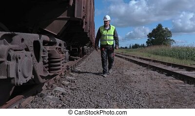 Railway worker inspecting wagon wheels