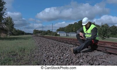 Railway worker sitting on rails and using tablet and walkie talkie
