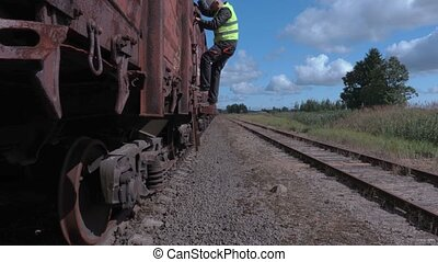 Railway worker using tablet and walking near wagons