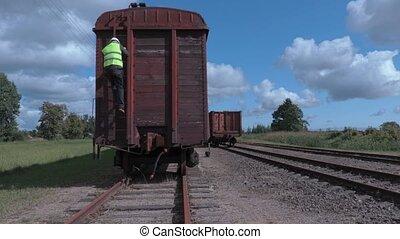 Railway worker using tablet near last wagon