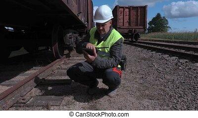 Railway worker using tablet near wagon wheels