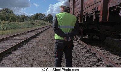 Railway worker with walkie talkie near wagons