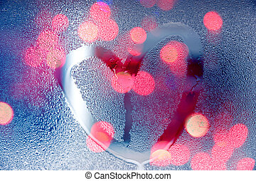 Rain at night, draw heart shape on wet glass with light