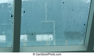 Rain drips over the dirty glass. Tropical rainfall in...