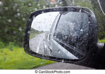 Rain drop on wing mirror or outside mirror of car while driving on road in rainy day. Drive carefully in rainy day to reduce accident.