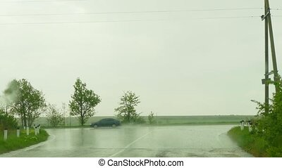 Rain drops fall on the windshield
