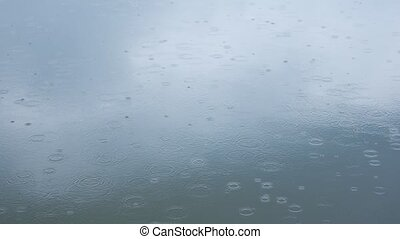 Rain drops fall on water surface of pond, lake or river forming a uniform background.