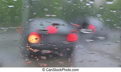 Rain drops falling on car windshield, blurred traffic ...