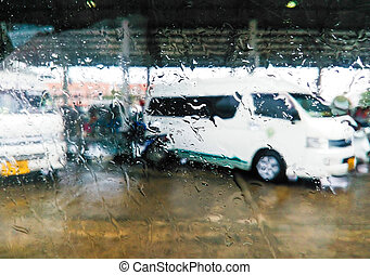 Rain drops on a car window and a view of the street in...