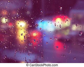 Rain drops on glass in urban environment.