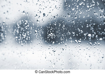 Rain drops on the glass window. Blurred background