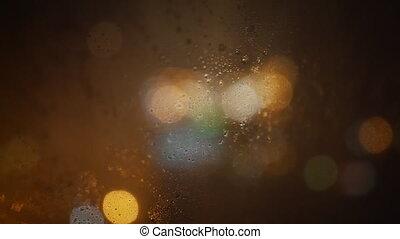 Rain drops on the window, defocused city lights