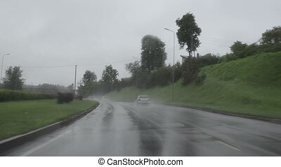 Rain falling and cars going on highway road. Front automobile window windscreen view and wipers work.
