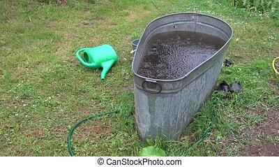 Rain fall in tin water reservoir in garden. 4K - Rain fall...