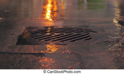 Rain falling in slow motion down a sewer drain at night. -...