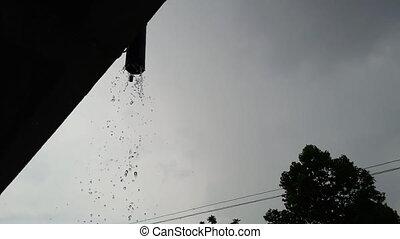 Rain falls from the gutter