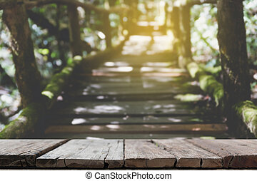 rain forest walk way in Ang Ka nature trail located in Doi inthanon national park, the highest peak in Thailand (blur image) with selected focus wood table for display your product
