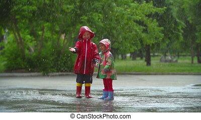 Rain Fun - Two kids having fun under umbrella bouncing in...