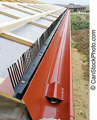 Gutter with downpipe for rain water collection  on the house under construction in construction site