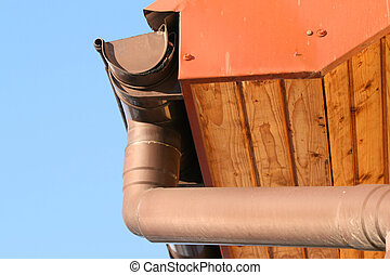 Rain gutter on house with blue sky in the background